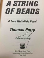 A STRING OF BEADS. by Perry, Thomas.